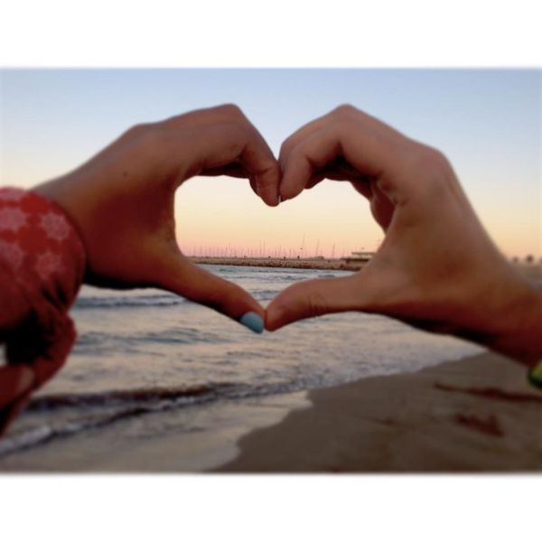 a symbol of love from the hands on the background of the sea