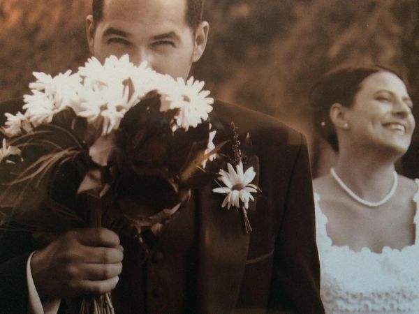 man giving his wife flowers at the wedding