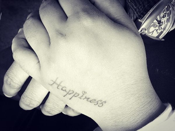 happiness tattoo text on hand